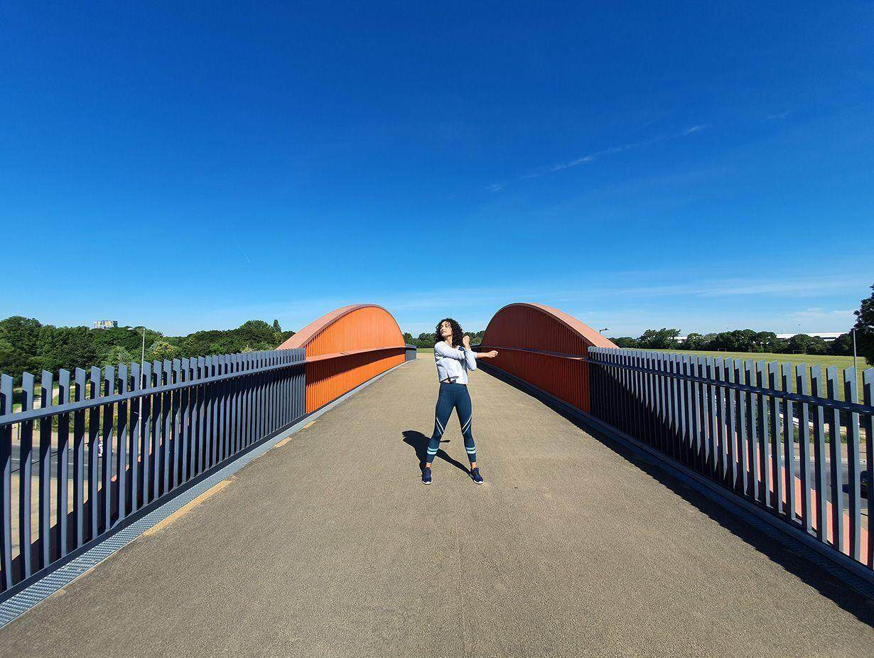 Photo captured by the Ultra Wide Camera of a woman stretching on a bridge with grey gating and orange accents against a bright blue sky